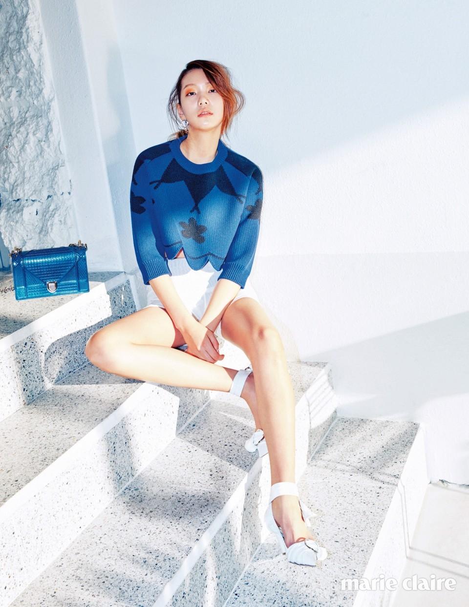 짙은 블루 컬러가 매력적인 니트 크롭트 톱과 화이트 쇼츠, 투명한 원석 싱글 이어링, 버클 디테일 화이트 스트랩 슈즈, 메탈 블루 컬러의 디올라마 백 모두 디올(Dior).