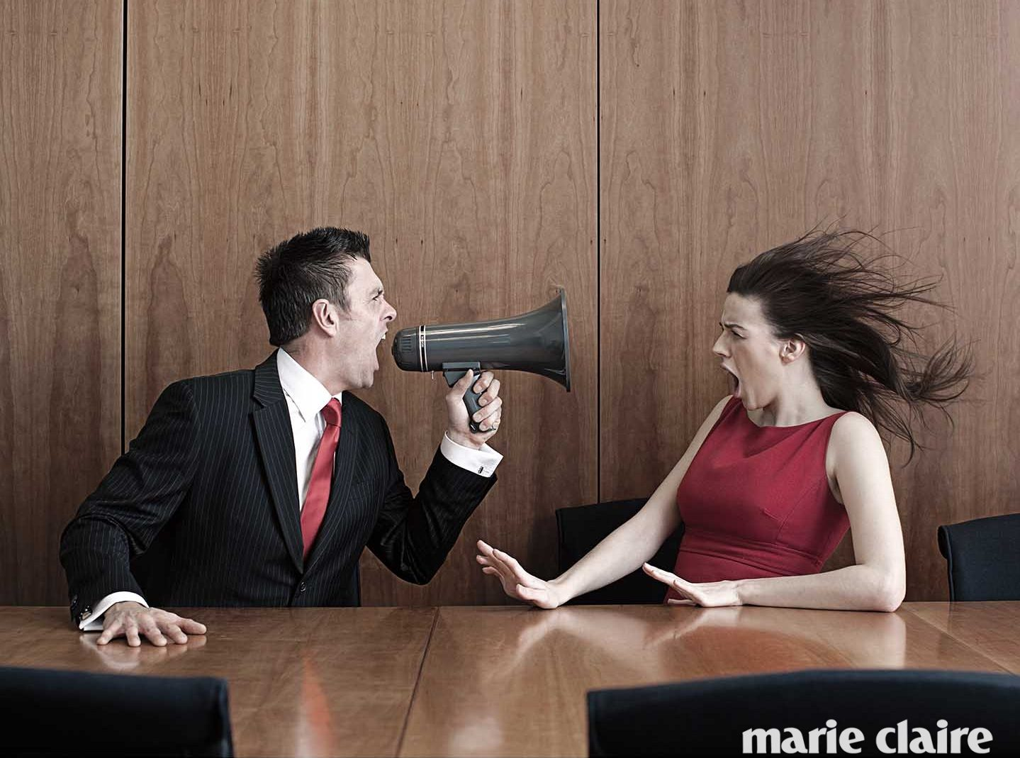 Businessman using megaphone to shout at female colleague