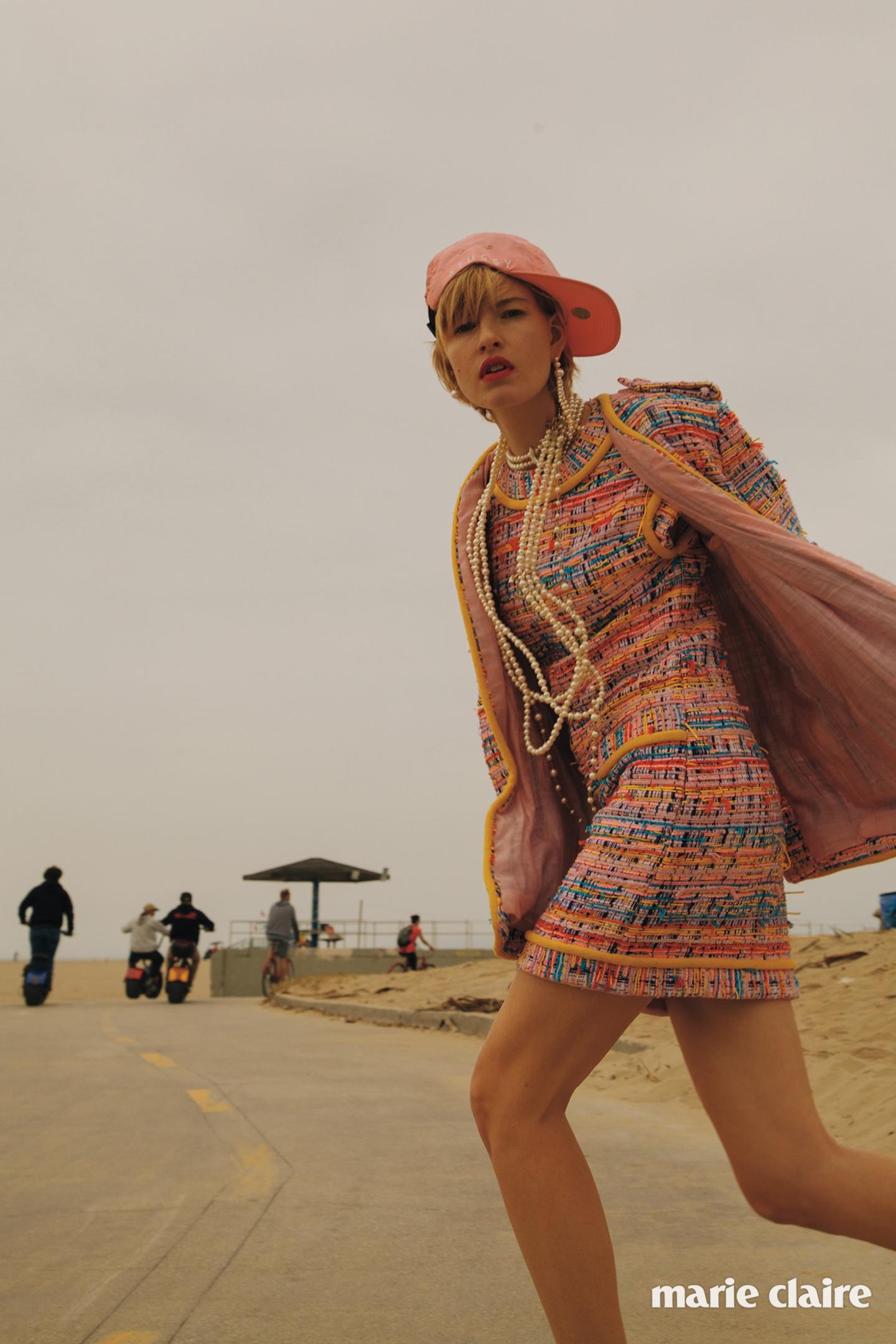 트위드 재킷과 트위드 드레스, 진주 초커와 목걸이 모두 샤넬(Chanel),오른쪽 귀의 진주 이어링 바우터스 앤 헨드릭스(Wouters & Hendrix),왼쪽 귀의 진주 이어링 사리나 수리아노(Sarina Suriano), 폴리에스테르 캡 스투시(Stussy).