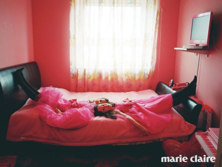 생일을 맞은 다섯 살 쌍둥이 소녀가 똑같은 드레스를 입고 방에 누워 있다.