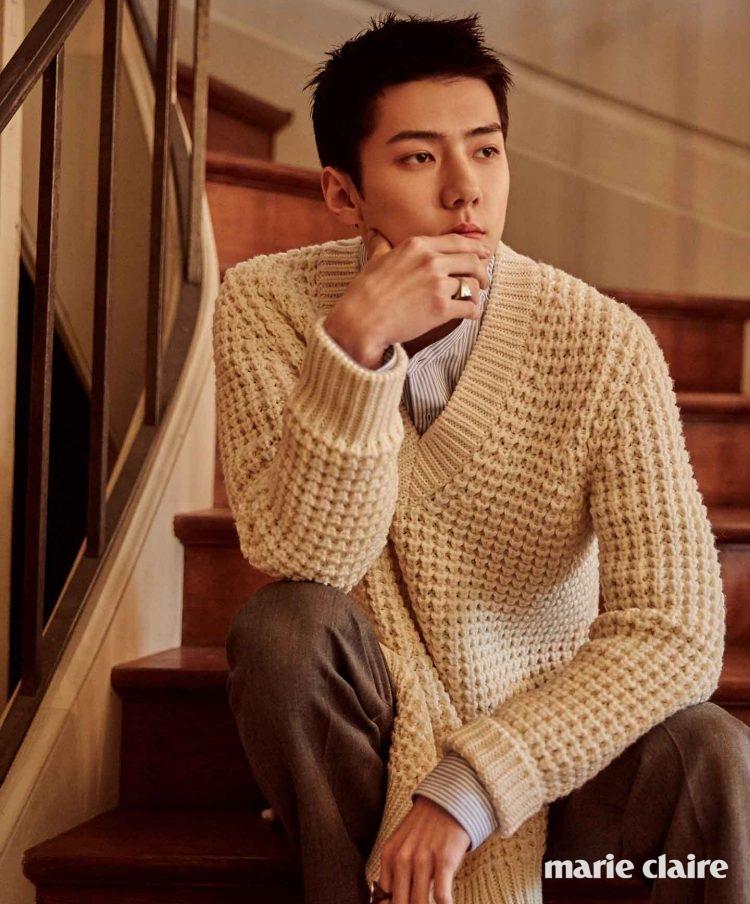 아이보리 브이넥 니트 스웨터, 핀스트라이프 셔츠, 그레이 팬츠, 볼드한 로고 장식 반지 모두 루이 비통(Louis Vuitton).