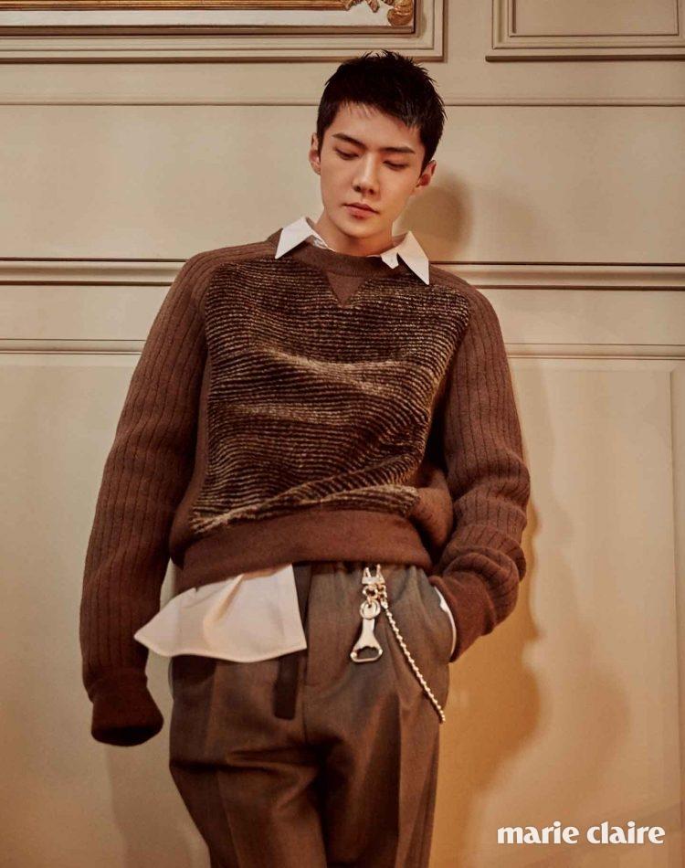 스웨트셔츠 디자인의 브라운 니트 스웨터, 화이트 셔츠, 그레이 팬츠, 벨트에 장식한 오프너 모양의 키링 모두 루이 비통(Louis Vuitton).