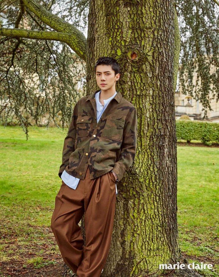카무플라주 패턴 재킷, 핀스트라이프 셔츠, 벽돌색 팬츠, 실버 컬러 네크리스 모두 루이 비통(Louis Vuitton).